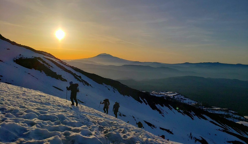 Hikers climbing the side of a mountain in the snow