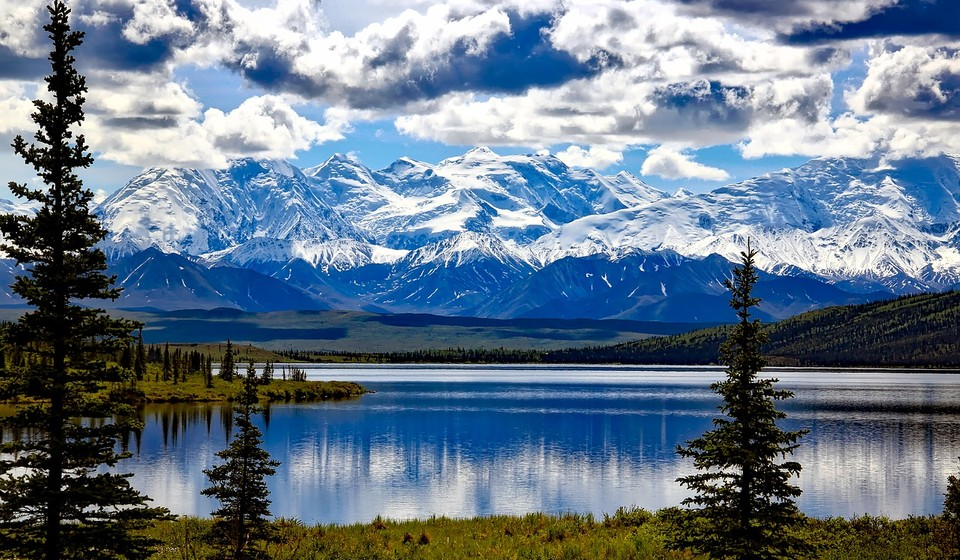 Alaskan tundra with lake, trees, and snowy mountains
