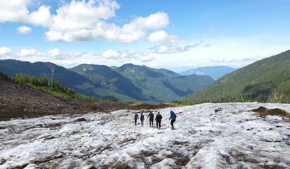Women walking on a glacier amidst mountains