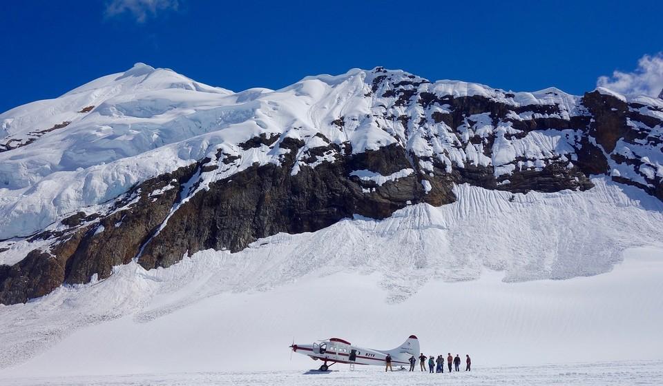 Passengers outside plane on Alaskan mountain