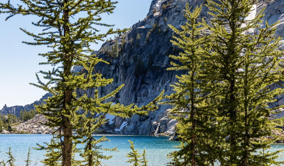 Blue lake, pine trees, and tall mountain cliff of Enchantment basin in Leavenworth