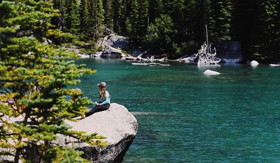 Woman sitting on rock at Colchuk Lake in Washington